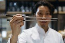 Крупным планом японского шеф-повара с палочками для еды — стоковое фото