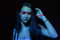 Молодий приваблива жінка з червоною лінією на обличчя і руки, дивлячись на камеру на чорному фоні — стокове фото