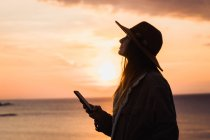 Woman in hat holding smartphone at seaside at sunset — Stock Photo