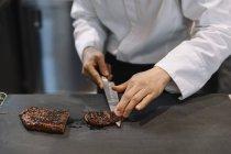 Trancher le bœuf grillé au restaurant de chef — Photo de stock