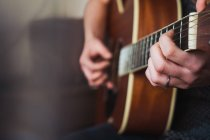Close-up of human hands playing acoustic guitar — Stock Photo