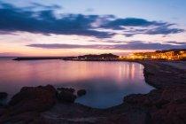Illuminated town and bay at sunset, Sardegna, Italy — Stock Photo