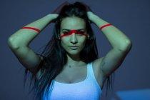 Молодий приваблива жінка з червоною лінією на обличчя і руки на темному тлі — стокове фото