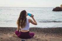 Fit woman sitting on shore at ocean and drinking water from bottle — Stock Photo