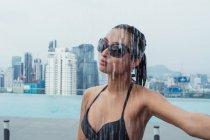 Красива жінка, що стоять біля басейну душ з хмарочоси на фоні — стокове фото