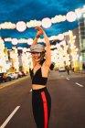 Модні молоді азіатські жінки прогулянки з підняв руки в місті освітленій у вечорі — стокове фото