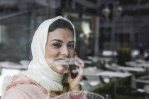Marokkanerin mit Hijab und traditioneller arabischer Kleidung telefoniert hinter Fensterscheibe — Stockfoto