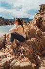 Femme assise sur des rochers au bord de la mer et regardant la vue — Photo de stock