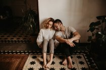 Romantic man and woman sitting on floor at home together — Stock Photo