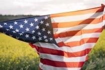 Mujer que sostiene la bandera americana en campo de flores amarillas en el día de la independencia - foto de stock
