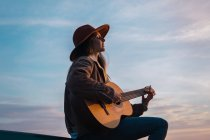 Woman sitting on car and playing guitar at sunset — Stock Photo