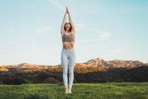 Femme méditant dans la nature avec des montagnes en arrière-plan — Photo de stock