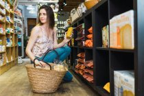 Woman picking product in food basket in supermarket — Stock Photo