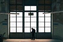 Turismo masculino parado na porta luz grande em prédio com câmera — Fotografia de Stock