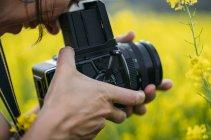 Close-up de mulher com foto tomada de câmera retro na natureza com flores amarelas — Fotografia de Stock
