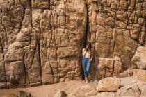 Topless attraente giovane donna in jeans in piedi e in posa a roccia ruvida — Foto stock