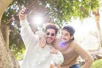Smiling happy male friends taking selfie with smartphone in sunny park — Stock Photo