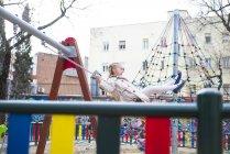 Souriant fille blonde balançant dans le parc — Photo de stock