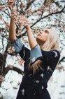 Donna bionda premurosa in piedi all'albero in fiore — Foto stock