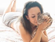 Young woman lying in bed with chinchilla — Stock Photo