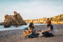 Sentado en la playa y tocar la guitarra para el hombre por una mujer bonita - foto de stock