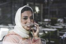 Moroccan woman with hijab and traditional Arabic dress talking on phone behind window pane — Stock Photo