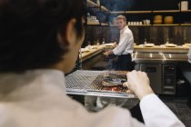Chef preparing beef roast in restaurant with colleague on background — Stock Photo