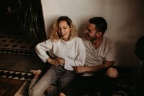 Cheerful man and woman sitting on floor and having fun at home — Stock Photo