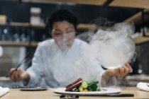 Chef de cocina en restaurante con plato humo - foto de stock