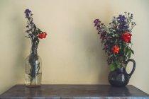 Вазы с цветами на столе перед стеной — стоковое фото