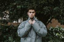 Молодий красивий підліток у сірому стильні Куртки утеплені стоячи перед зелене дерево — стокове фото
