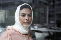Nachdenkliche marokkanische Frau mit Hijab blickt hinter Fensterscheibe in die Kamera — Stockfoto