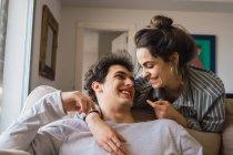 Casal jovem alegre, rindo de sofá — Fotografia de Stock