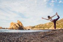 Фитнес-женщина, растягивающаяся в стороне от камней — стоковое фото