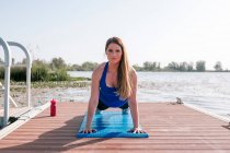 Portrait of young woman doing sport on pier at lake — Stock Photo