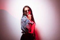 Спокушання молоду жінку в сонцезахисні окуляри, стоячи біля білі стіни і дивлячись на камеру — стокове фото