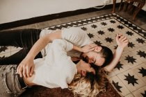 Happy romantic man and woman lying on floor and kissing at home — Stock Photo