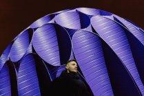 Людина, що стоїть перед великий синій сфері пам'ятник, освітлені вночі, порту, Португалія — стокове фото