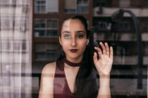 Portrait of young woman behind window with the reflection of building — Stock Photo