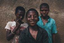 Camarões - África - 5 de abril de 2018: Alegres africanos rapazes valentes na parede áspera e olhando para a câmera — Fotografia de Stock