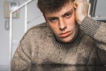 Freckled uomo in maglione che tiene la testa e che guarda l'obbiettivo — Foto stock