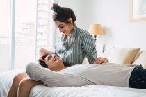 Веселый молодой человек лежал на коленях подруги на кровати у себя дома — стоковое фото