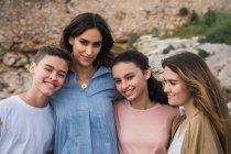 Portrait of woman and teenagers standing outdoors — Stock Photo