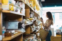 Young woman picking up jam jar in store — Stock Photo