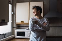 Jovem alegre de pé com xícara de café e olhando para a janela na cozinha — Fotografia de Stock