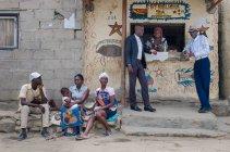 ANGOLA - ÁFRICA - 5 DE ABRIL DE 2018 - Hombres y mujeres africanos de pie en el escaparate de la tienda del pueblo en la calle de la ciudad - foto de stock