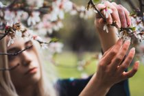 Jeune femme blonde debout à arbre fleurissant et toucher la fleur — Photo de stock