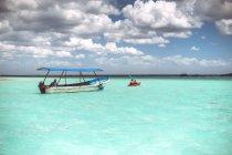 Лодки в бирюзовый Карибского моря с пасмурным небом, Мексика — стоковое фото