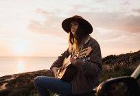 Mujer sentada en coche y tocando la guitarra en la costa al atardecer - foto de stock