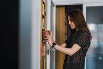 Jovem mulher de pé na prateleira e tendo discos compactos em casa — Fotografia de Stock